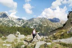 一座高山的远足者妇女在Vihren峰顶背景 免版税库存照片
