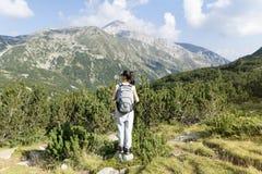 一座高山的远足者妇女,看全景 图库摄影