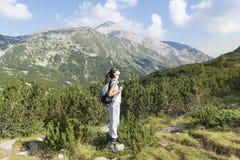 一座高山的远足者妇女,看全景 库存照片