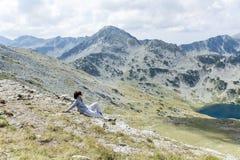 一座高山的远足者妇女,看全景 免版税库存图片