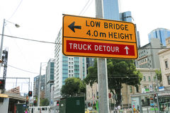 一座黄色和黑'Low桥梁, 4m Height'和'Truck Detour'在碎片街道路轨桥梁附近签字 库存图片