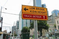 一座黄色和黑'Low桥梁, 4m Height'和'Truck Detour'在碎片街道路轨桥梁附近签字 免版税库存照片
