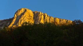 一座Miroc山的垂直的峭壁在日落的在Djerdap国家公园,从河多瑙河的射击 库存照片