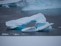 一座Smalled被成拱形的冰山在南极洲 免版税库存图片