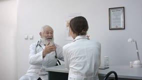 一张书桌的一位资深男性医生在办公室微笑和谈话与女性医生 影视素材