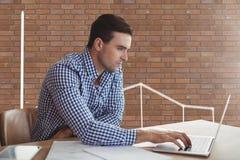 一张书桌的商人使用一台计算机对有图表的砖墙 免版税库存照片