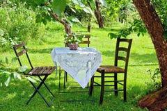 一张咖啡桌的美丽如画的设置在庭院里 免版税库存照片