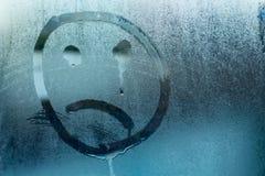 一张哭泣的面孔的图象在玻璃的 库存照片