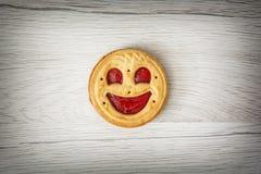 一张圆的饼干微笑的面孔,幽默甜食物 免版税库存照片