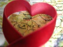 一张地图集地图的巴黎法国与在它附近的红色丝带心脏 免版税库存照片