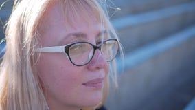 一张女性面孔的特写镜头 白发开发在风下 女孩坐体育场的指挥台 股票视频