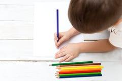 一张孩子图画的手与在纸的 平的位置 免版税图库摄影