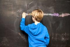 一张小男孩绘画的后面看法某事在黑板 免版税库存图片