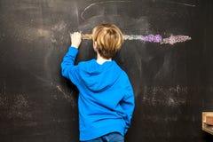 一张小男孩绘画的后面看法某事在黑板 免版税库存照片