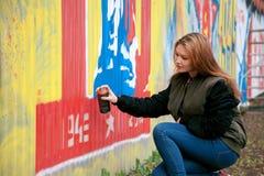 一张少妇绘画街道画的画象与喷漆的在街道墙壁上 在露天 城市概念 免版税库存照片