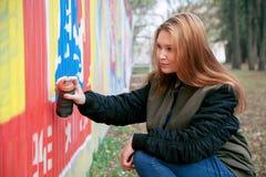 一张少妇绘画街道画的画象与喷漆的在街道墙壁上 在露天 城市概念 免版税库存图片