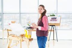 一张少妇画家图画的画象与水彩调色板的在使用画架的纸 免版税库存图片