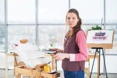 一张少妇画家图画的画象与水彩调色板的在使用画架的纸 库存照片