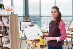一张少妇画家图画的画象与水彩调色板的在使用画架的纸 免版税库存照片