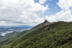 一张山岩石面孔的水平的广角看法与有些树的在与白色云彩的蓝天下- pico e serra做lopo 免版税库存图片