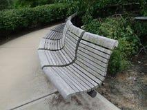 一张弯曲的木材公园长椅在一个公园 免版税库存照片