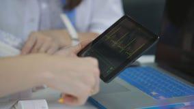 一张心电图的特写镜头在一种片剂的在坐在他的办公室的医生的手上在诊所 影视素材