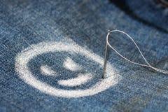 一张快乐的面孔的图象,微笑,画与在牛仔裤的白垩 针和线程数 库存照片