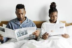 一张愉快的夫妇读书报纸在床上 库存图片