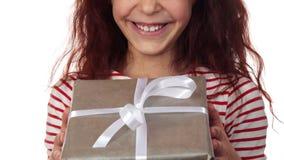 一张愉快的女孩面孔的特写镜头与一件新年礼物的在手上 库存照片