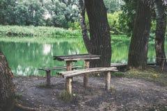 一张木桌和一条长凳在河岸 一个美好的安排 库存照片