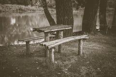 一张木桌和一条长凳在河岸 一个美好的安排 免版税库存照片