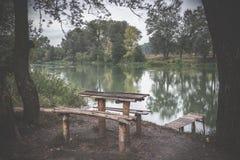 一张木桌和一条长凳在河岸 一个美好的安排 免版税图库摄影