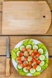 一张木桌是刀子,并且一个切板和在一块白色板材是切的黄瓜,蕃茄 免版税库存照片