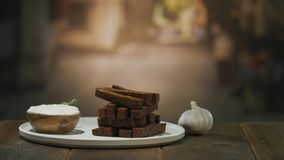 一张木桌服务用油炸油煎方型小面包片和蒜酱油在碗 影视素材