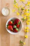 一张木桌的顶视图与花装饰,碗的可口红色和新鲜的草莓和小碗新鲜的干酪 免版税库存照片