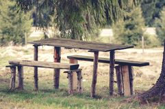 一张木,土气长凳和野餐桌的葡萄酒照片 库存图片
