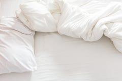 一张没有整理好的床的顶视图与枕头、床单和毯子的 免版税库存照片