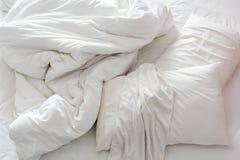 一张没有整理好的床的顶视图在有被弄皱的床单的一间卧室 免版税图库摄影