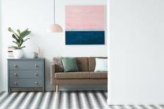 一张洗脸台、植物、棕色沙发和绘画的真正的照片在liv 库存图片