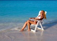 一张海滩睡椅的年轻俏丽的妇女在海洋 免版税图库摄影