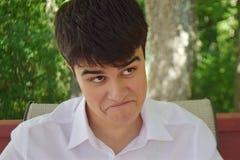 一张滑稽的面孔的逗人喜爱青少年 免版税库存图片