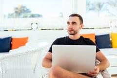 一张甲板海滩睡椅的英俊的人与在线的笔记本,在聪明的舒适的甲板享用并且放松 免版税库存照片