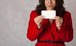 一张白色卡片在一个少妇的手上 库存照片