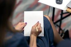一张白色纸片的女孩作家 库存图片