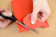 一张礼品券华伦泰` s天卡片的生产与鸽子的 逐步的过程:心脏的切口准备 免版税库存图片