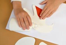 一张礼品券华伦泰` s天卡片的生产与鸽子的 逐步的过程:把胶浆放在鸟的准备上 图库摄影