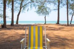 一张空的黄色海滩睡椅由显示通风天气的杉树海滩投入了 免版税库存图片