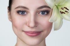 一张美丽的年轻蓝眼睛的女孩面孔的画象与一白色l的 库存图片