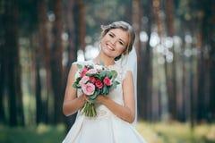 一张美丽的新娘画象在森林惊人的年轻新娘是难以置信地愉快的 衣物夫妇日愉快的葡萄酒婚礼 免版税库存图片