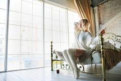 一张美丽的早晨照片在一间白色织地不很细卧室 白色毛线衣和白色的一个少妇编织了高尔夫球 免版税图库摄影
